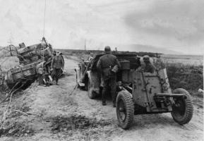 Расчет немецкой пушки PaK 35/36 осматривает сгоревший советский тягач «Ворошиловец»