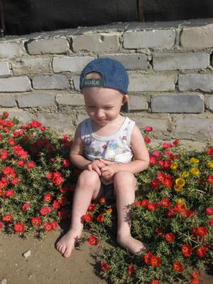 Внуку очень нравится сидеть в цветах...
