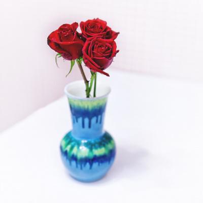 Три красные розы в синей вазе
