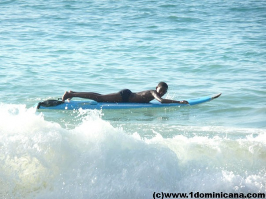 Юный серфер учится ловить волну