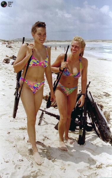 Американские женщины-военнослужащие гуляют по пляжу в Могадишо о своим оружием, 11 июля 1993: