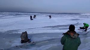 Рыбаки убегают от волны, которая разрушает лед