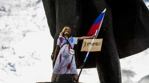 «Против нищеты и полицейского государства»: студентка в сорочке и с флагом РФ приковала себя к памятнику Ленину в Новосибирске