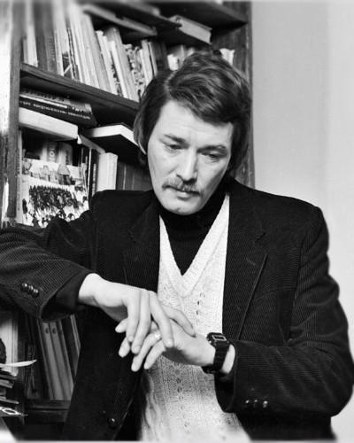 Игорь Старыгин на фоне книжной полки в собственной квартире в начале 90-х прошлого века