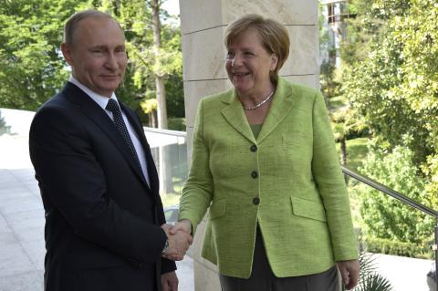Канцлер улыбается. Путин жмет руку