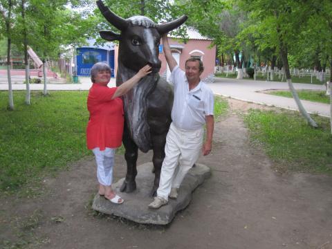 На мфоне фигуры быка я и мой муж в парке 2011 год