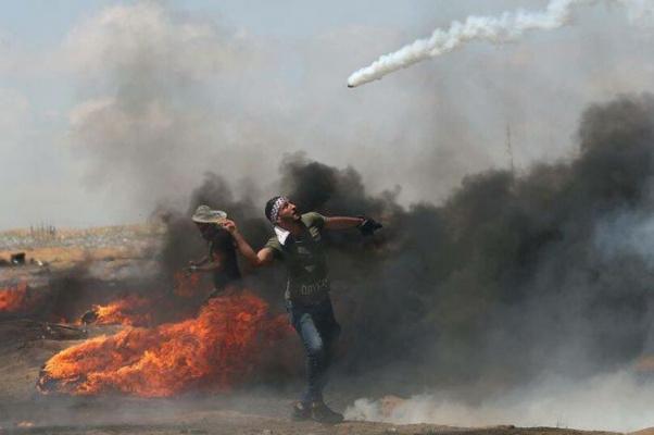 Палестинский протестующий использует теннисную ракетку, чтобы отбить гранату со слезоточивым газом